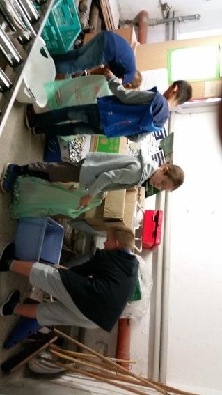 Schüler der Umwelt-AG beim Umfüllen der gesammelten Deckel und Kronkorken für den Abtransport
