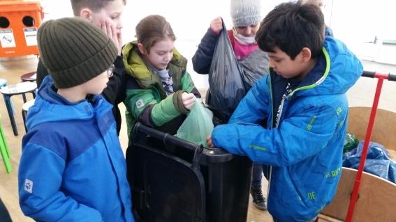 Bei ALBA, Schüler beim Befüllen der Tonne mit den mitgebrachten Kronkorken